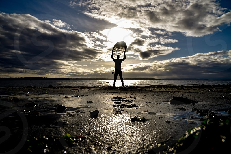 Surfboard overhead man holding above head surfer sunset sunrise sandy beach summer sand waves silhouette photo