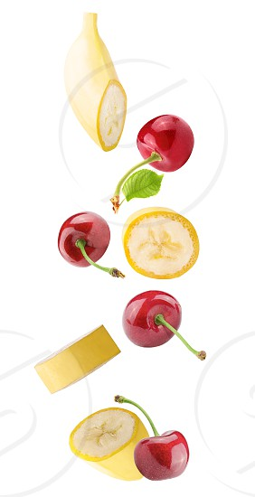 Isolated flying fruits. Falling banana and cherry fruits isolated on white background with clipping path as package design element and advertising. photo
