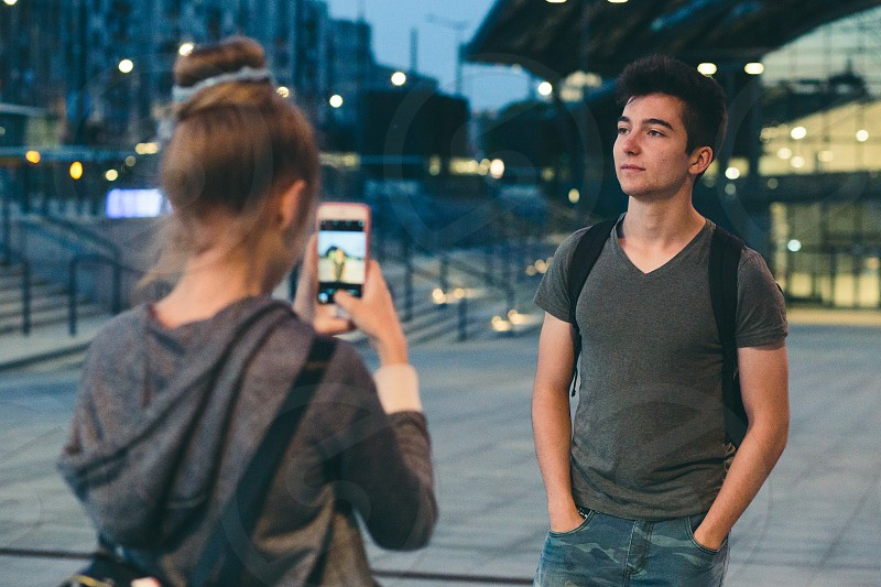 Young woman taking photos her friend using a smartphone in the city at night photo
