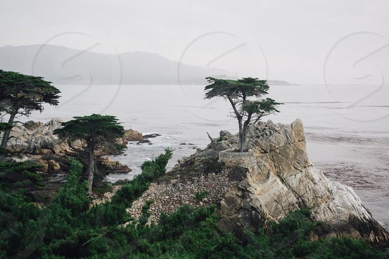 beige rock monolith near body of water under cloudy sky photo