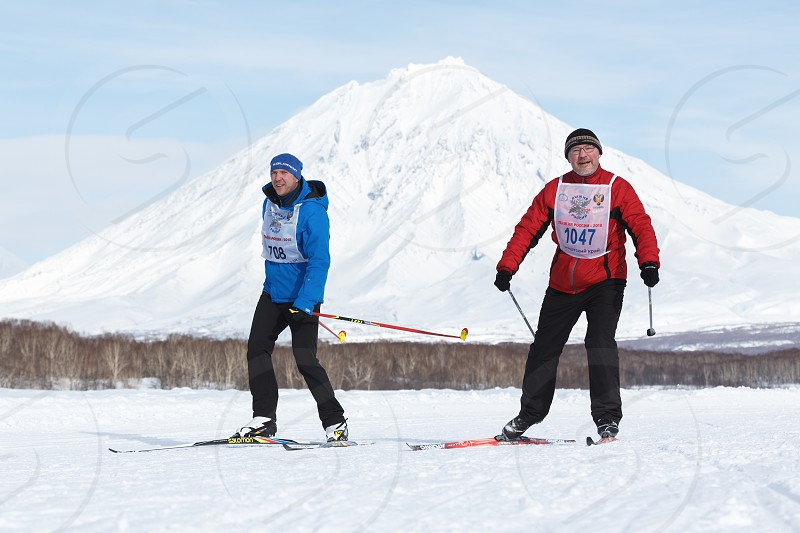 PETROPAVLOVSK CITY KAMCHATKA PENINSULA RUSSIAN FAR EAST - FEB 10 2018: Skiers-men running along the winter ski track on background of Koryak Volcano. All-Russia mass ski race - Ski Track of Russia. photo