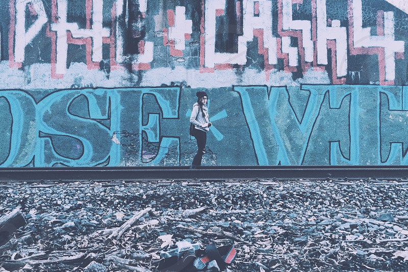 woman carrying camera standing in between rail track beside graffiti wall photo
