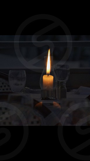 A candle on a kitchen table in the center of another candle holder from a restaurant in Key West Florida.  photo