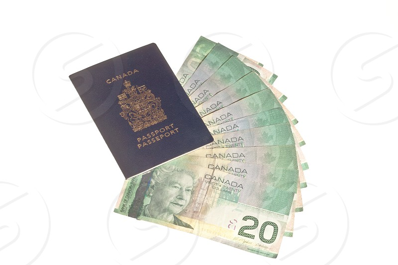 Canadian passport and Canadian money twenty dollar bill bank notes isolated on white background photo