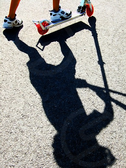 Long shadow of a child on a scooter only his feet and scooter base show. photo