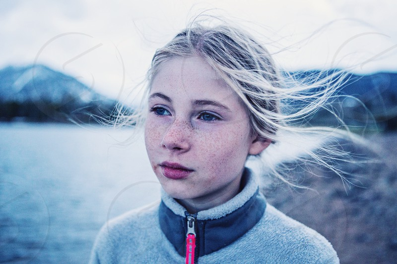 little girl looking at lake while wind blows her hair  photo