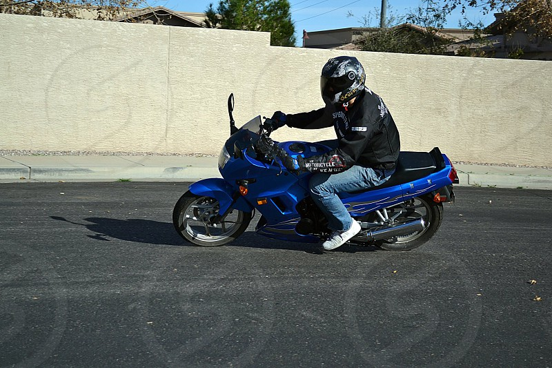 20 year old male driving around the neighborhood testing his new motorcycle out. Blue sportsbike photo