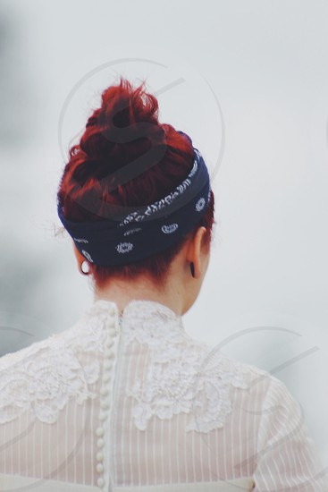 standing red-haired woman wearing white blouse with small buttons up the back and black bandana around her hair photo