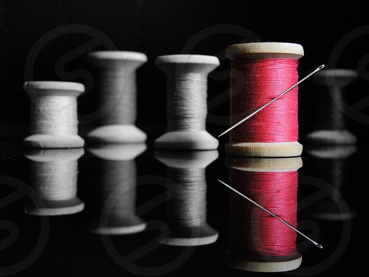 silver metal needle through red thread spool reflected with grey thread spools behind photo