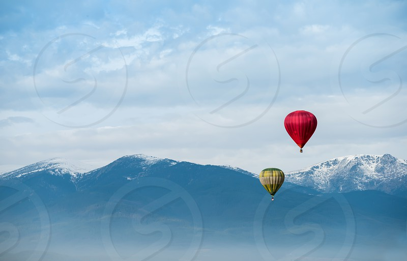Red balloon in the blue cloudy sky photo