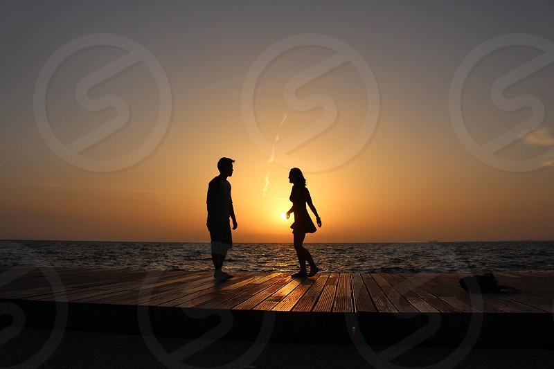 silhouette of man and woman standing on brown boardwalk near blue ocean water under orange sunset photo