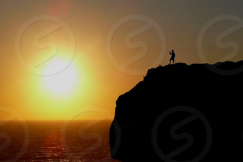 man at the cliff under the sunset by the ocean photo
