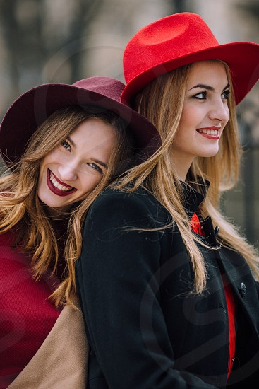 smiling woman in red leaning on another smiling blonde woman in red and black looking away photo