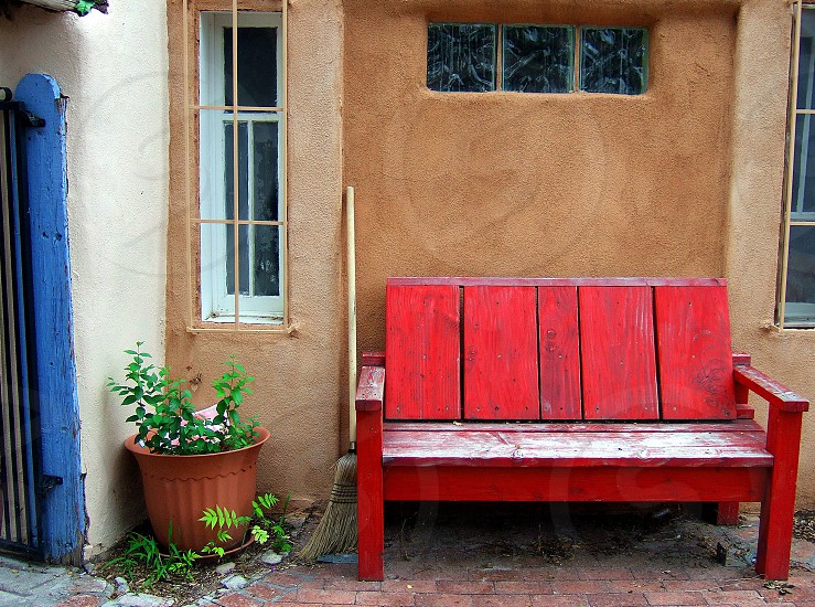 Rustic weathered red bench  outside A wall of an Adobe home P photo