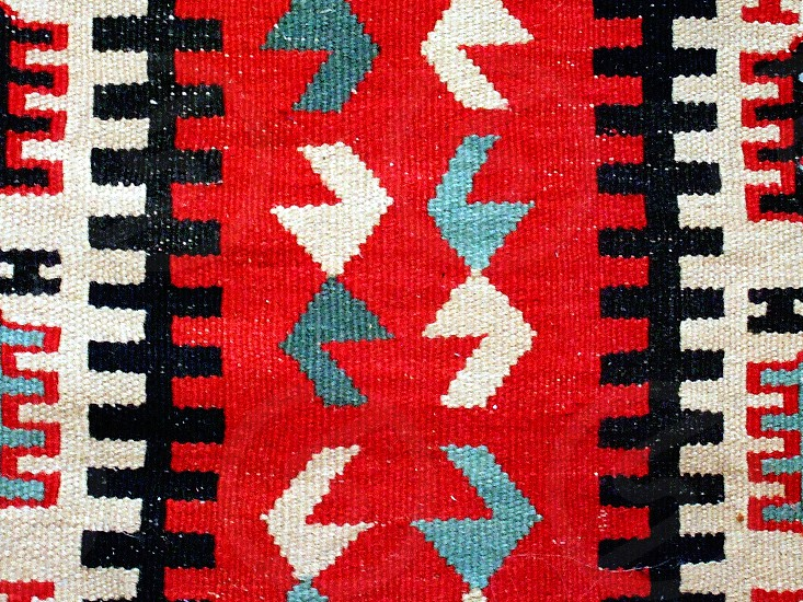 A detail of a Navajo blanket with a geometric design in red black and gray. photo