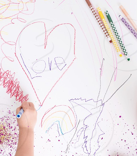 Kids little girl art play coloring drawing colored pencils create creative heart rainbow hand arm fingers photo