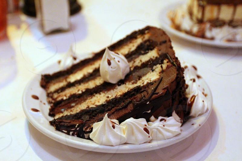 Three chocolate cake with white milk and dark chocolate and whipped cream photo