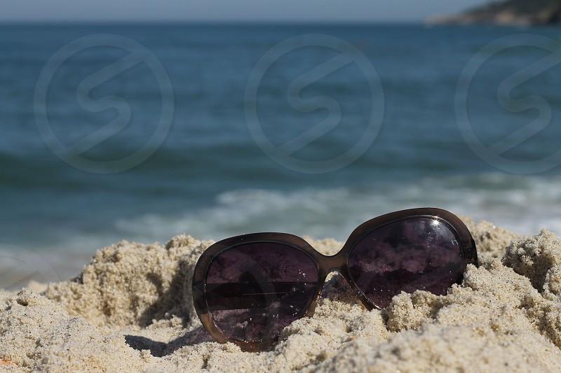 sunglasses on sand at sea side photo