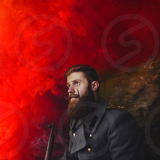 man in black coat holding vintage rifle under red cloudy sky photo