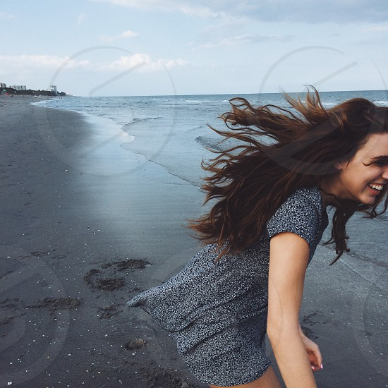woman in gray cap sleeve romper smiling standing sea shore at daytime photo