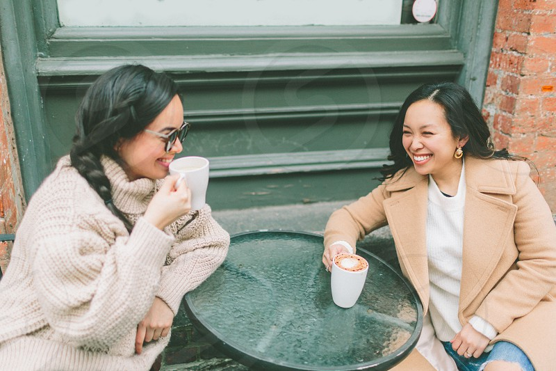 Two friends having coffee outside of a cafe. photo