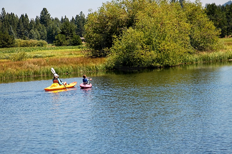 From a distance two people in kayaks paddle down a river photo