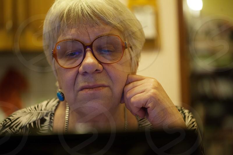 Close-up shot of elderly woman having emotional skype talk using laptop photo