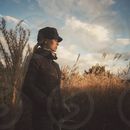woman wearing black jacket standing near brown weeds photo