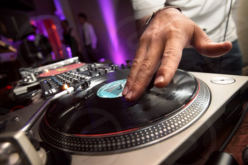 Closeup on the hands of a DJ spinning vinyl records. photo