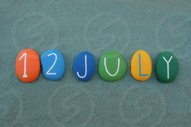 12 July calendar date composed with multi colored stones over green sand photo