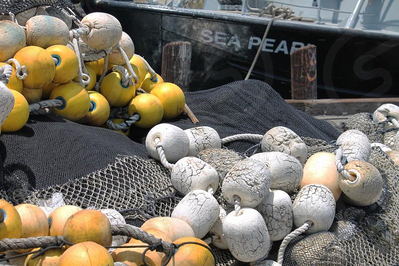 White and yellow fishing buoys on a fishing net photo