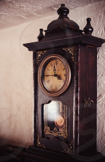 On old vintage style clock in front of a wall. photo