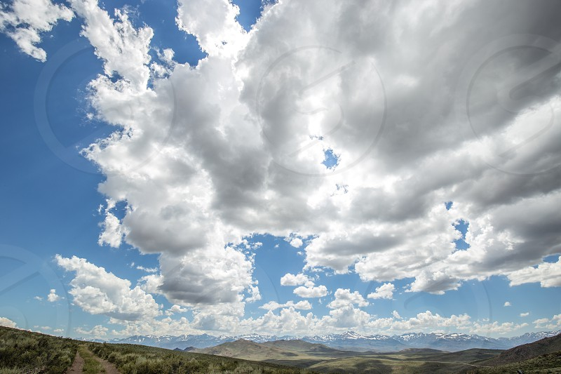 Storm clouds with snow covered mountain range in the distance photo