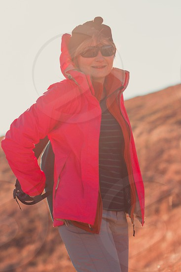 Woman putting a backpack on during a trip in the mountains on sunny windy autumn day. Direct sunlight into a lens. Woman wearing sports clothes smiling and looking at the camera photo
