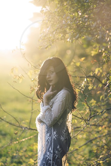 woman in white and black lace dress beside green leaf tree filtered with sunlight during day time photo