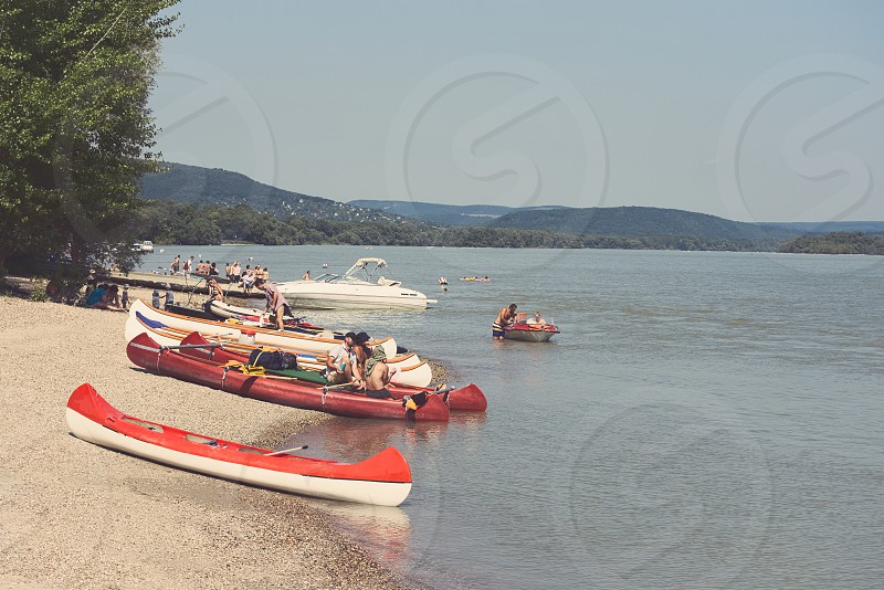 Vacation People on the Danube Beach with Red Canoe photo