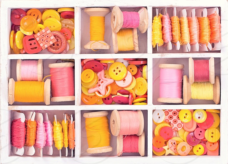 Collection of yellow red pink spools  threads on in a white wooden box photo