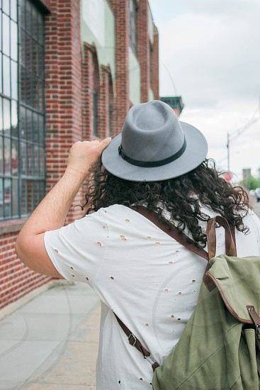 person in white t-shirt and gray fedora hat walking near brown building during daytime photo