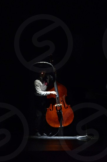 Mexican Mariachi band cello player performing music on stage in the spotlight photo