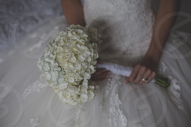wedding dress gown bouquet flowers wedding day marriage nuptials celebrations bride bridal white lace hydrangea floral arrangement wedding ring engagement ring ring happy celebrate ever after photo
