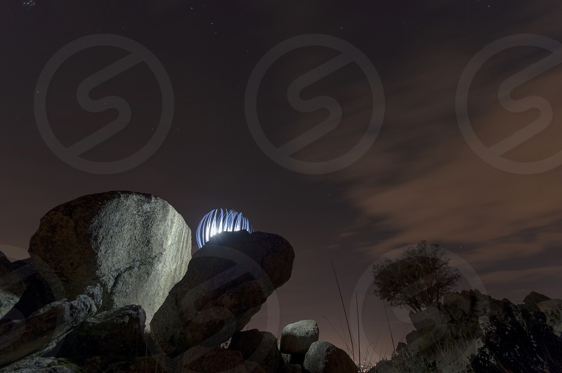 Painting a luminous sphere on the rocks of the hill at night photo