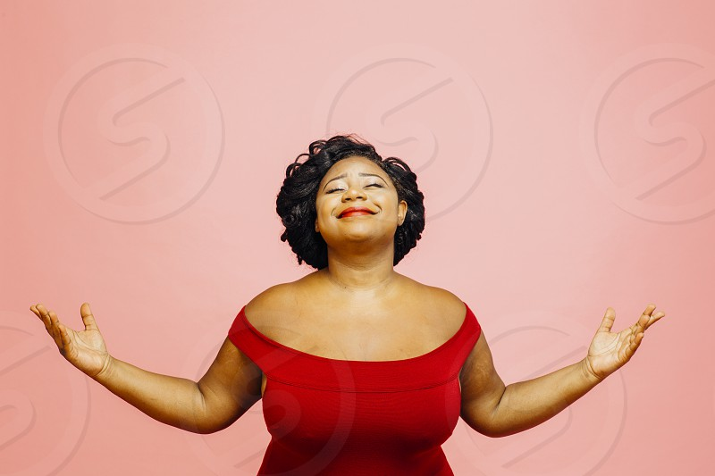 Life is wonderful/ Portrait of a confident satisfied and happy woman with both hands out isolated on pink photo