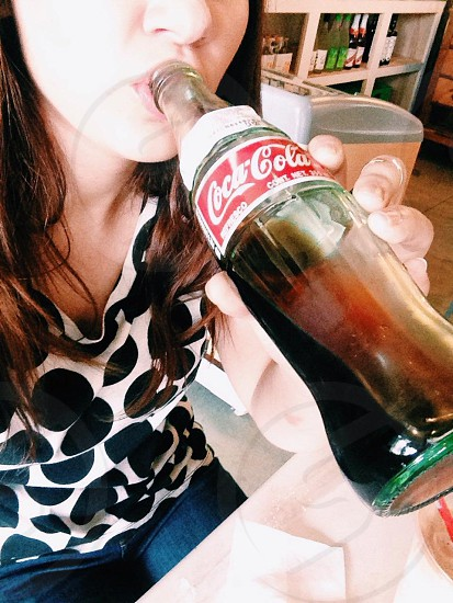 woman wearing black and white polka-dot shirt drinking Coca-Cola photo