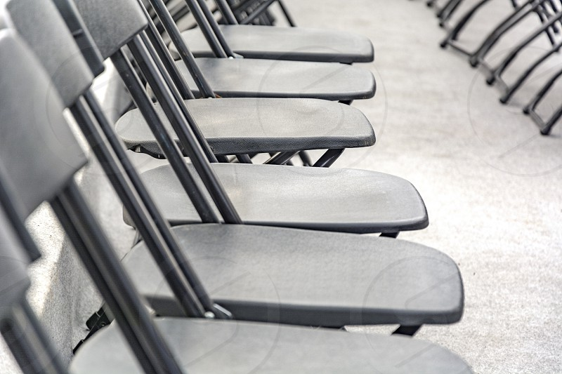Rows of black folding chairs empty in a conference room photo