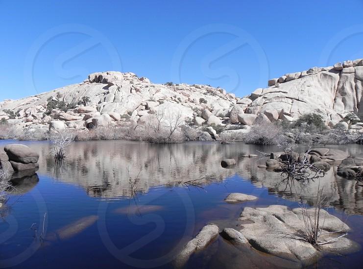 gray mountain near calm body of water photo