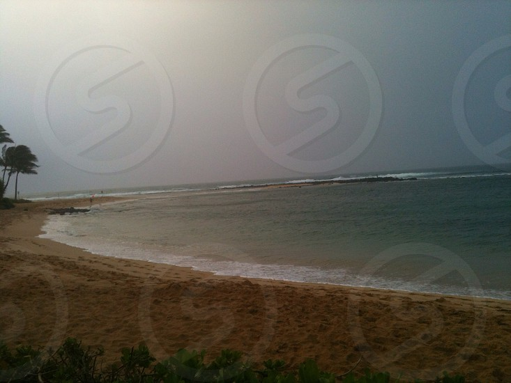 ocean and shore under gray cloudy sky photo