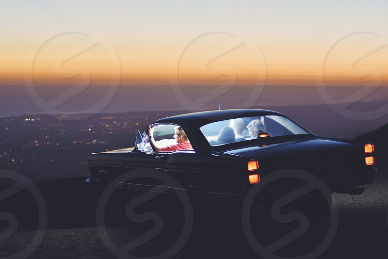vintage black two door car with four people parked on hill overlooking cityscape at sunset photo