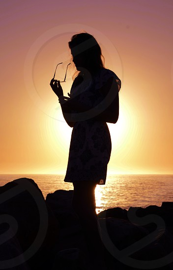Silhouette of woman with sunglasses on rocks by the ocean beach with bright summer sunlight at sunset photo