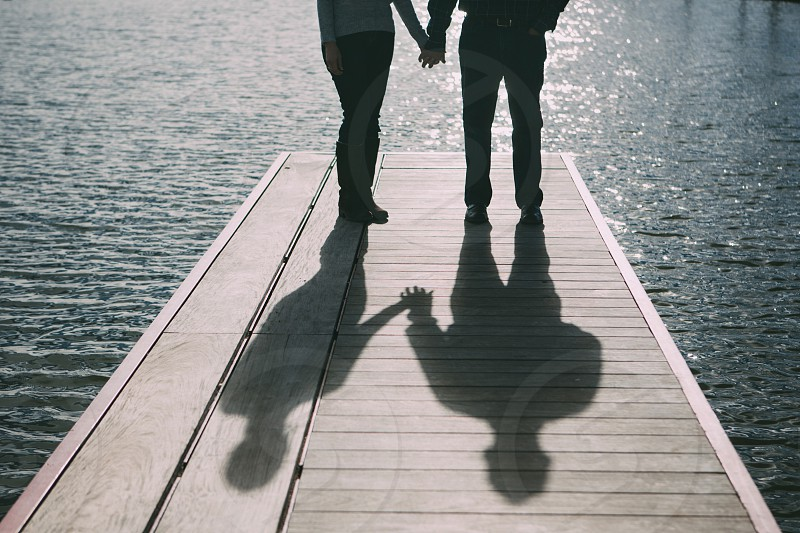 love marriage couple middle age organic holding hands shadow play shadow lake pier dock wood happy photo