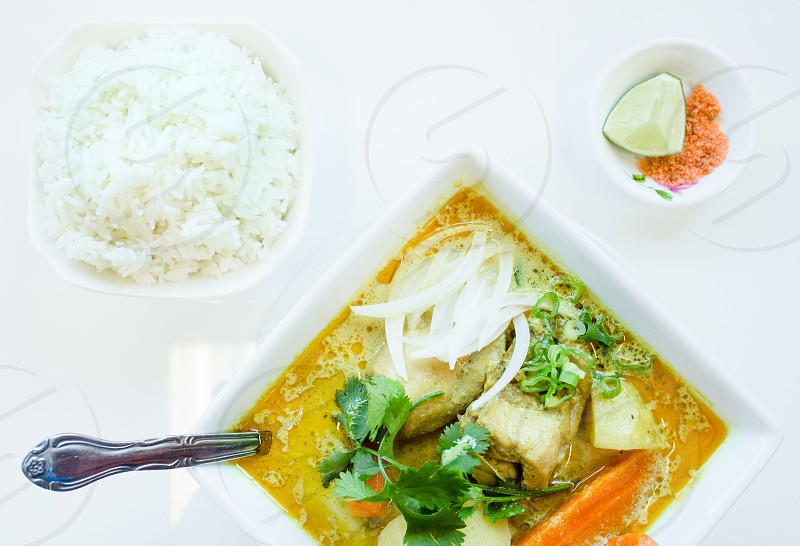 chicken curry with garnished paisley leaf and slice onion photo